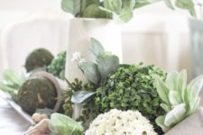 a dough bowl with moss and boxwood balls, fake blooms and greenery in a vase is a pretty rustic centerpiece