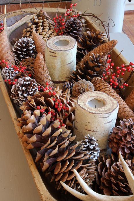 a dough bowl with pinecones of various sizes, with fake berries and birch branch candle holders