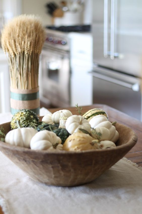 a dough bowl with various pumpkins is an easy and cool fall centerpiece