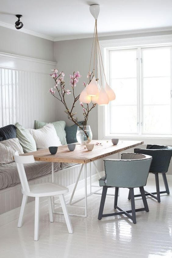a dreamy Nordic dining space with a built-in bench and muted pillows, a wooden table, muted color chairs and a cluster of pendant lamps