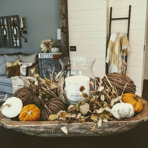 a fall decoration of a weathered dough bowl, fake pumpkins of various materials, dried leaves and a pillar candle
