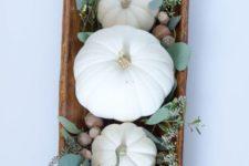 a farmhouse fall centerpiece with a dough bowl, acorns. fresh eucalyptus and milk paint pumpkins