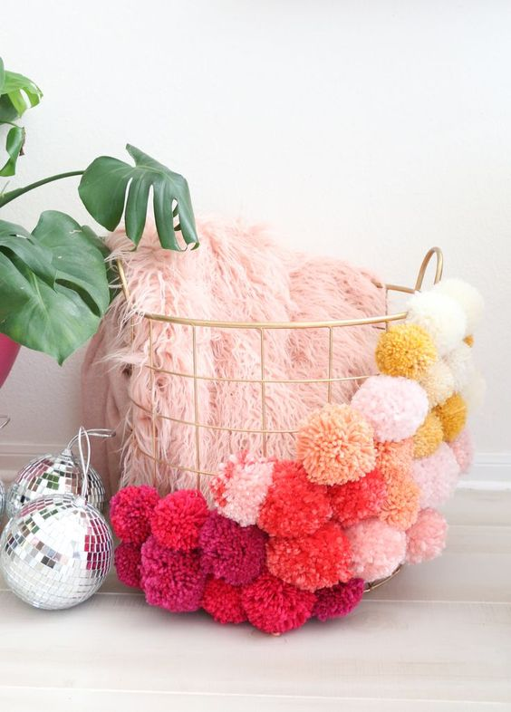a gold wire basket with colorful ombre pompoms covering it is a very fun and cool idea for decor