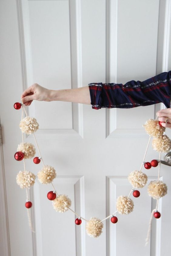 a gorgeous holiday garland of white pompoms and red ornaments to decorate your Christmas tree