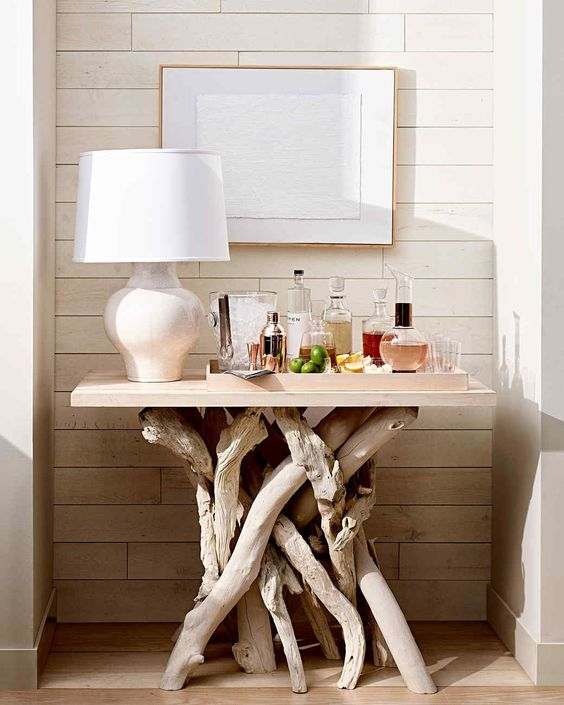 a home bar placed on the whitewashed driftwood is a cool and bold idea with a coastal feel