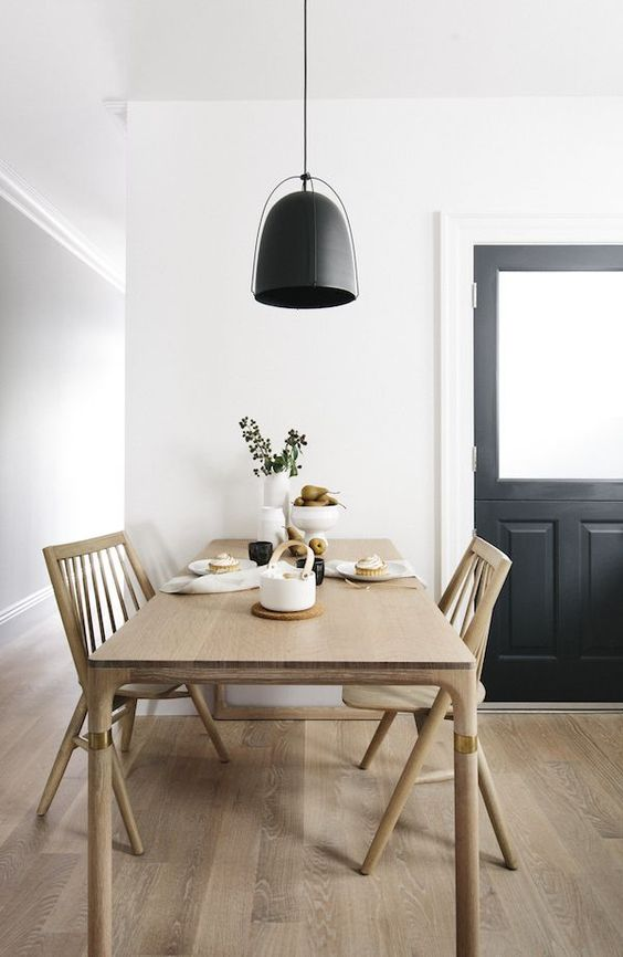 a laconic Nordic dining room with a sleek stained table and chairs, a black pendant lamp and greenery is super cool