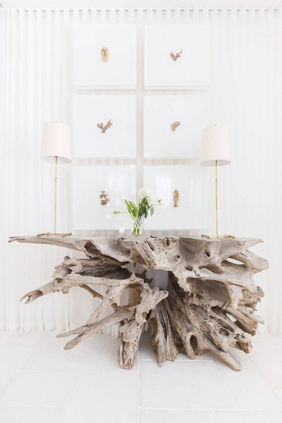 a large and dimensional console table made of driftwood is a stunning statement for a beachy entryway