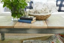 a large antique dough bowl is used to store magazines and newspapers under the coffee table