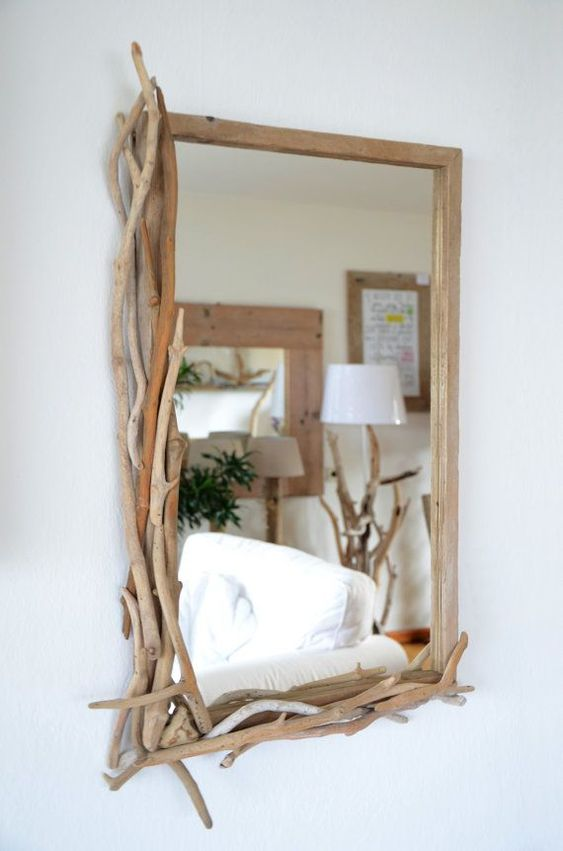 a mirror partly decorated with driftwood is a cool and chic idea to make your space relaxed and beachy
