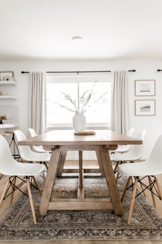 a modern Scandi dining room with a stained trestle dining table, white chairs, a printed rug, a vase with greenery