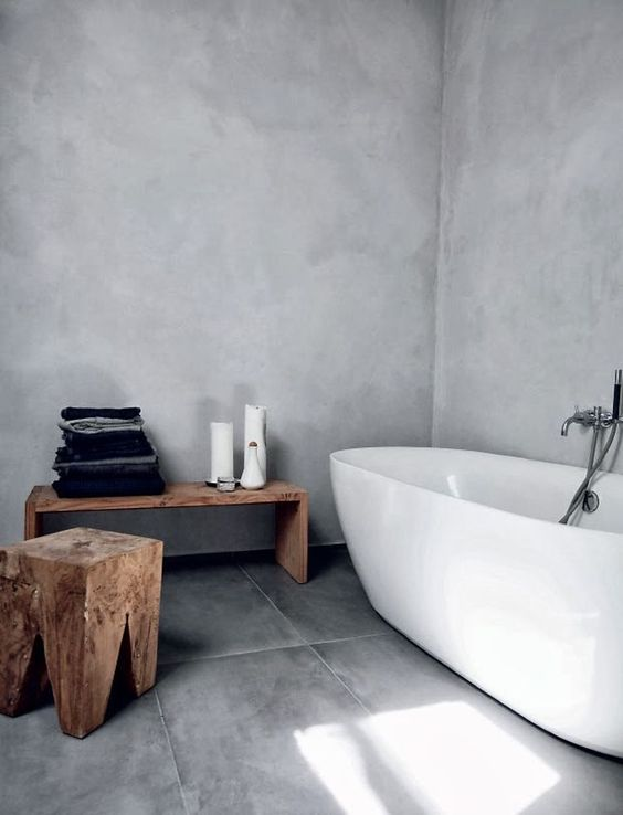 a natural Scandinavian bathroom done with concrete and grey tiles plus wooden stools and a bench