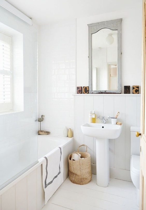 a neutral and cute bathroom with a Nordic feel, a basket for storage, a vintage mirror and whiet tiles