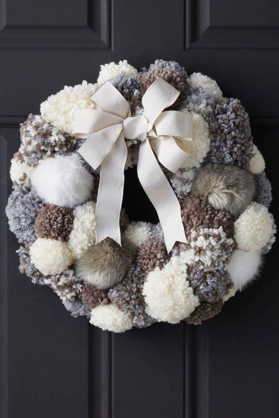 a neutral fluffy pompom wreath with a large creamy bow is a stylish and cozy decoration for your front door