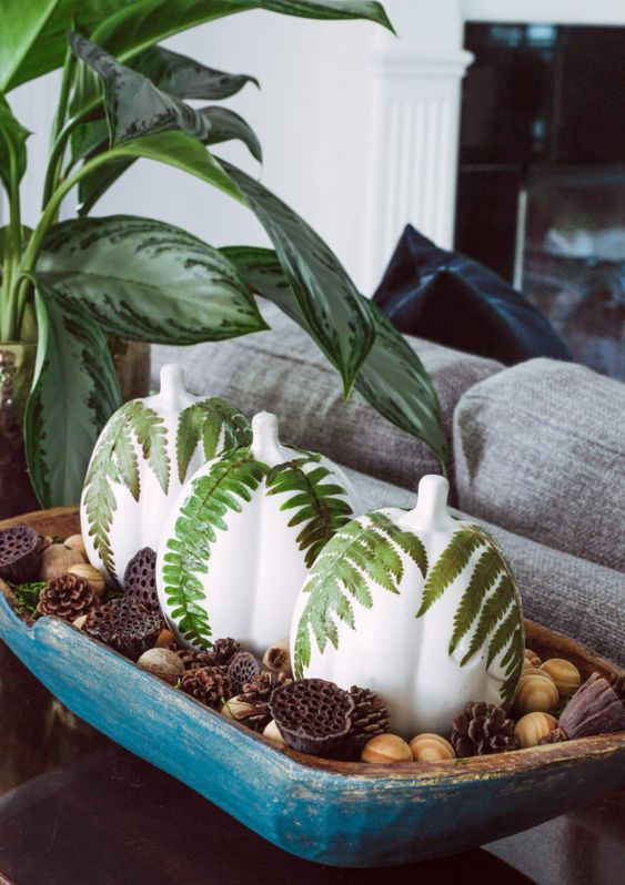 a painted blue dough bowl with nuts, painted pumpkins with fern leaves, lotus and pinecones
