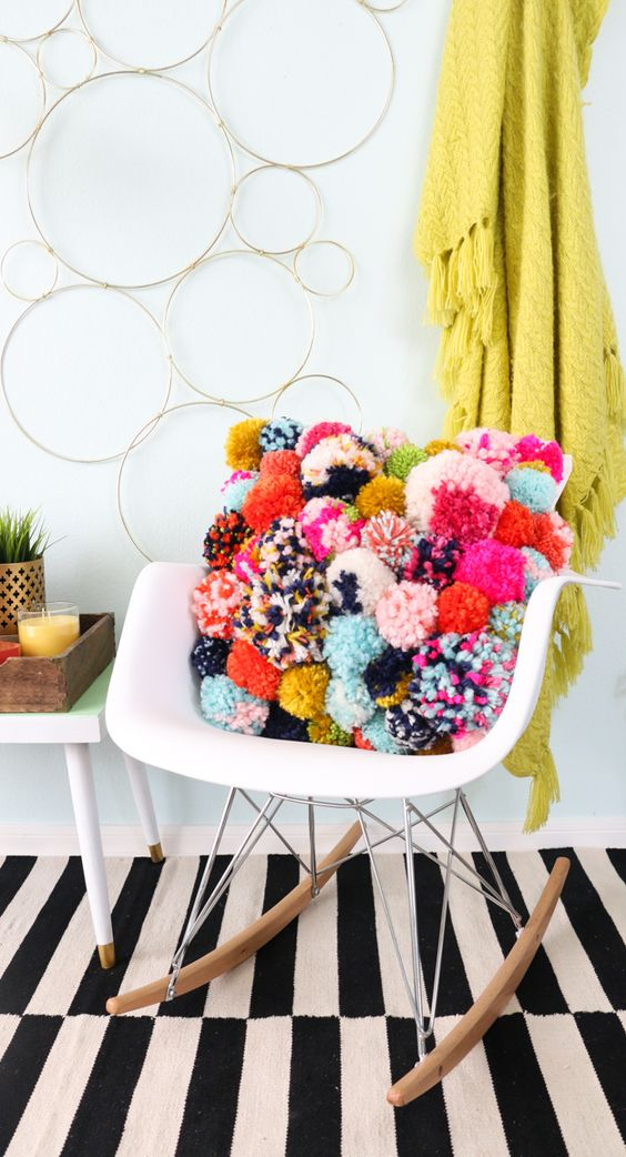 a pillow fully made of colorful pompoms is a very bright and cool decoration to accent your interior