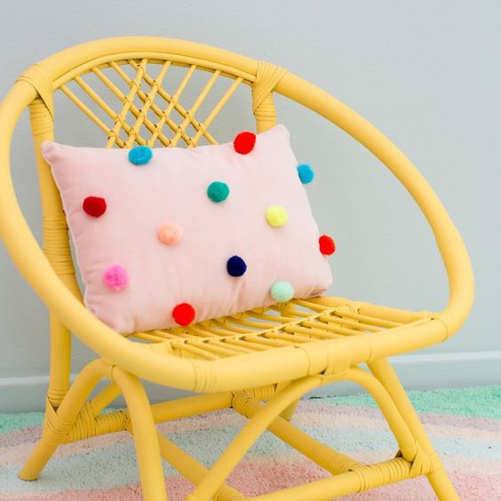 a pink pillow with colorufl pompoms accenting it is a cheerful and bright accessory that you can easily DIY