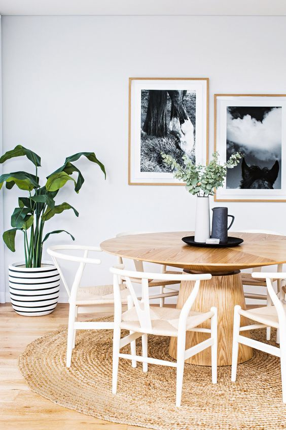 a pretty Nordic dining space with a round stained table, woven chairs, a jute rug, a mini gallery wall and a potted plant