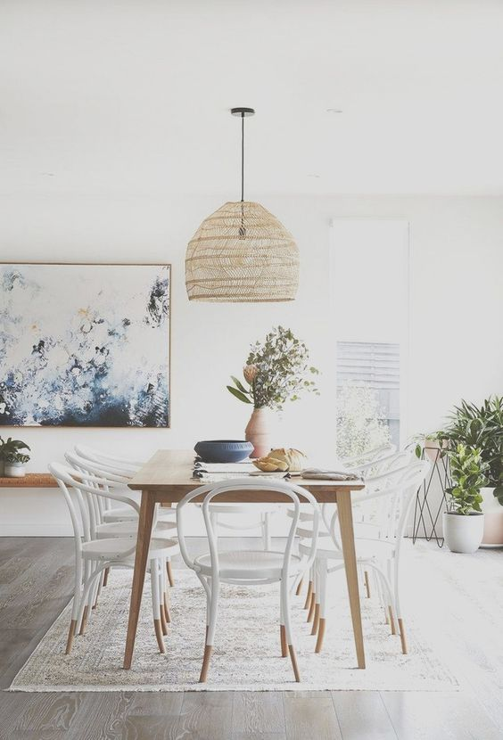 a pretty Scandinavian dining room with a sleek table, white and stain matching chairs, a woven pendant lamp and potted plants
