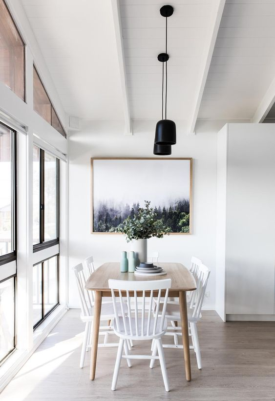 a pretty Scandinavian dining space with a stained table, white chairs, a chic print, black pendant lamps and pastel vases