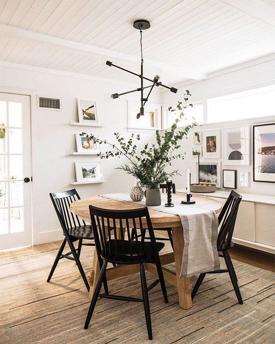 a pretty modern Nordic dining room with a round stained table, black chairs, a chandelier, a gallery wall and ledges with art