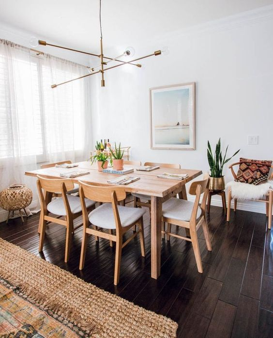 a pretty modern Scandinavian dining space with a stained table and neutral chairs, a dreamy artwork, a cool chandelier and faux fur