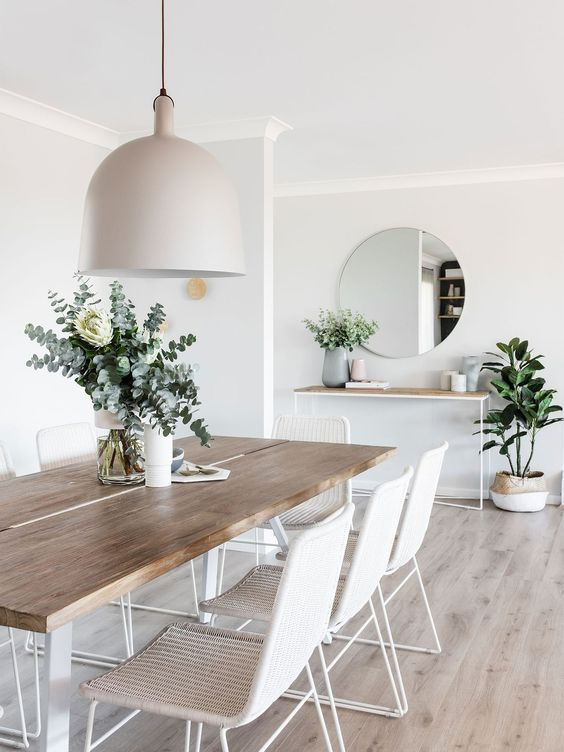 a refined Scandinavian dining room with a sleek table, white woven chairs, a tan pendant lamp and potted plants