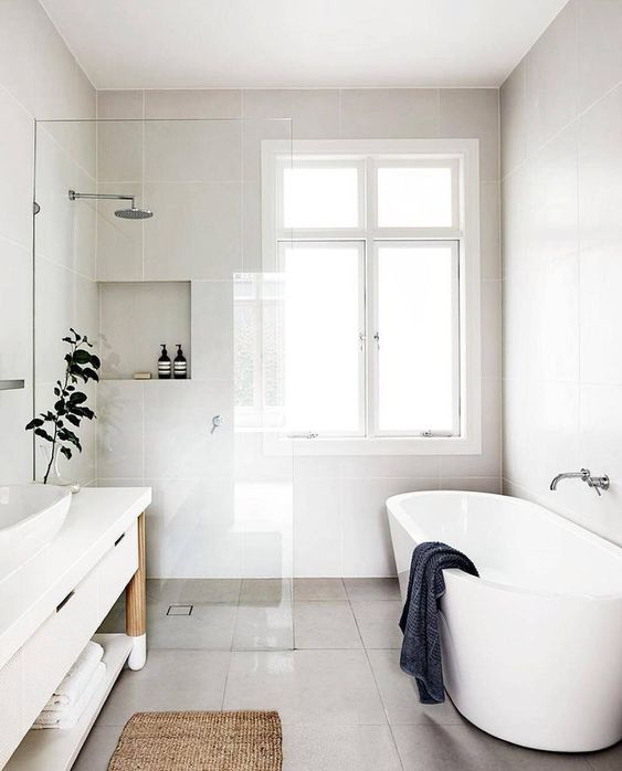 a refreshing Scandinavian bathroom with white walls, an oval tub, a long white vanity and a jute rug