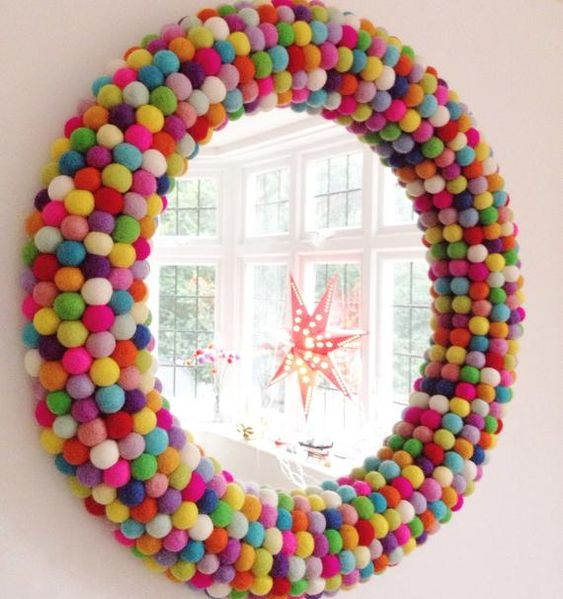 a round mirror covered with colorful pompoms to make it brighter and cooler is a bold accessory