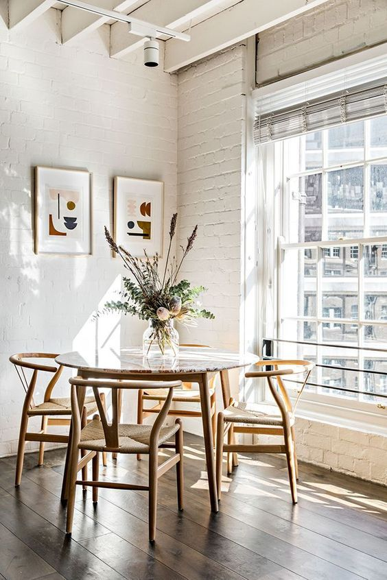 a round table with a bright tabletop, woven chairs, a muted color mini gallery wall and a floral arrangement with greenery