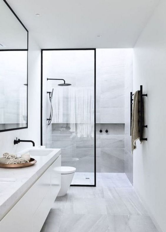 a serene Nordic bathroom with grey marble tiles, a long vanity and touches of black