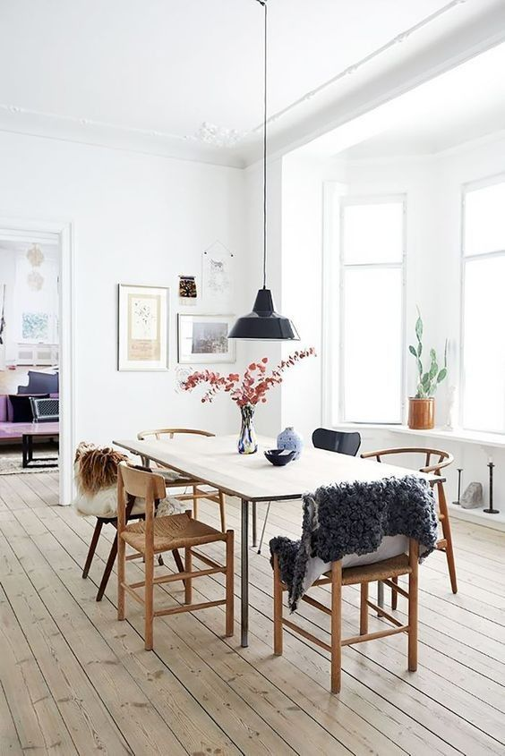 a serene and airy dining space with a sleek dining table, mismatching chairs, a black pendant lamp and a muted color gallery wall