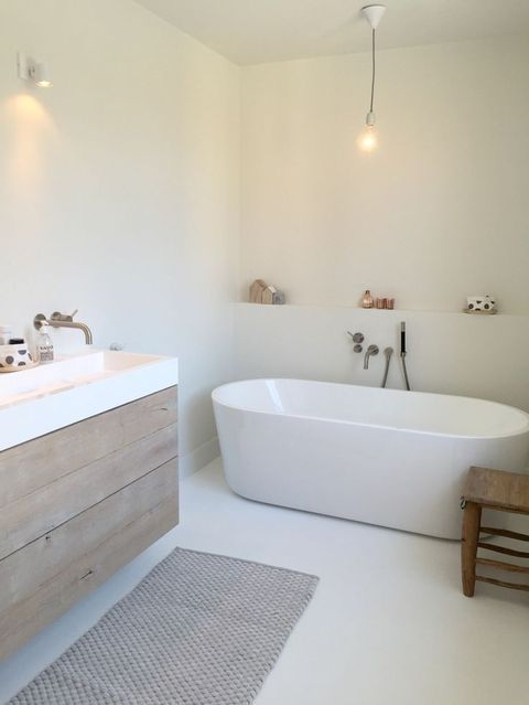 a serene white Nordic bathroom with an oval bathtub, a wooden vanity and a cozy rug