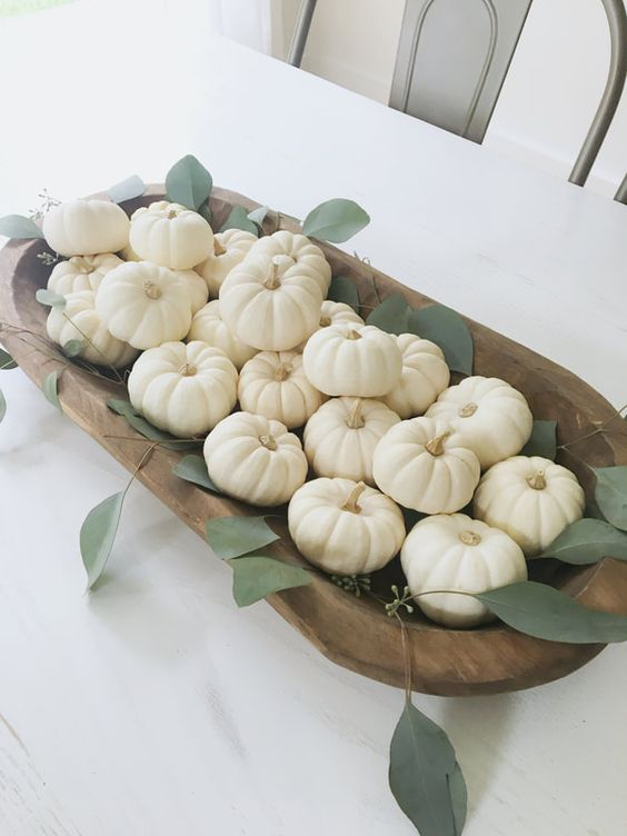 a simple and elegant fall centerpiece of a dough bowl filled with white pumpkins and some greenery