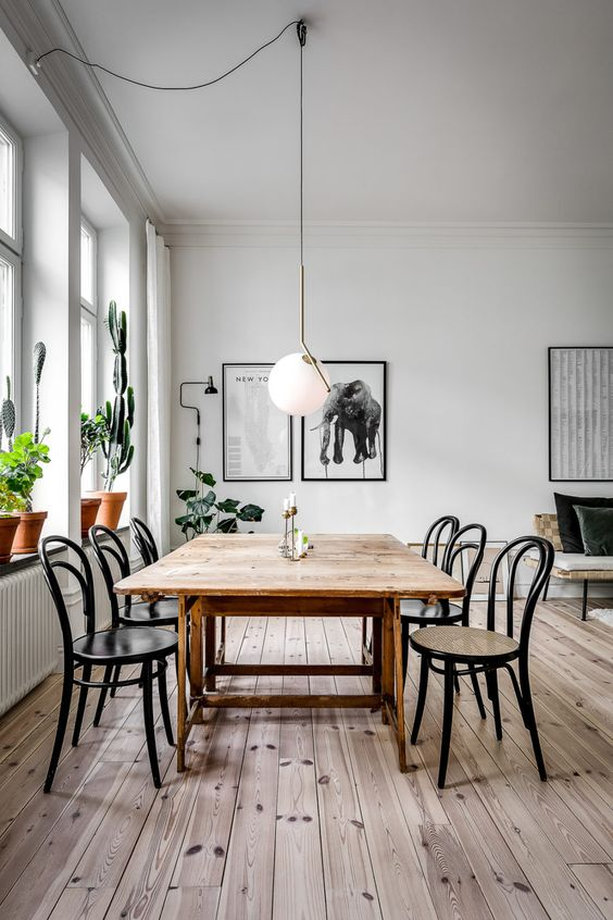 a simple and serene dining space with a stained wooden table, matching chairs, potted plants and a statement pendant lamp
