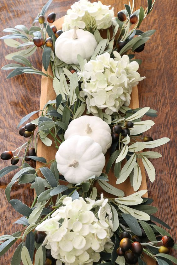 a simple neutral fall DIY centerpiece using a vintage rustic dough bowl, hydrangeas, olive branches and milk paint pumpkins