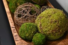 a simple rustic centerpiece with a dough bowl, moss and twine balls is a natural decoration