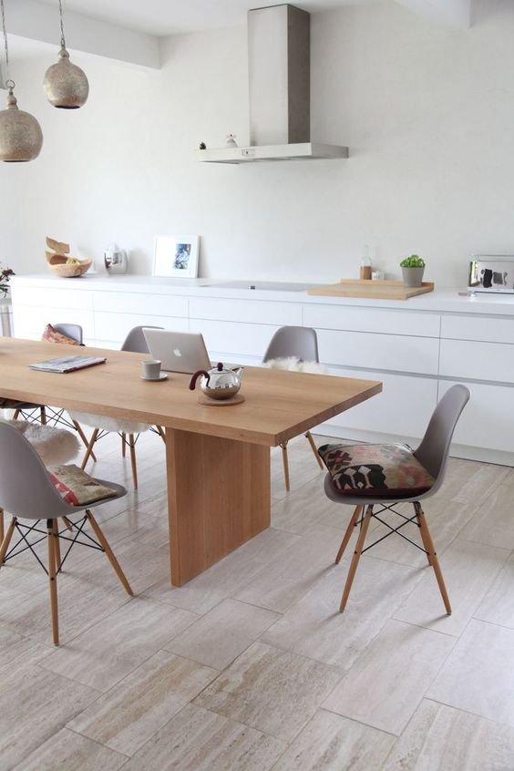 a sleek Nordic dining room with a light-stained table and matching grey chairs plus metal pendant lamps