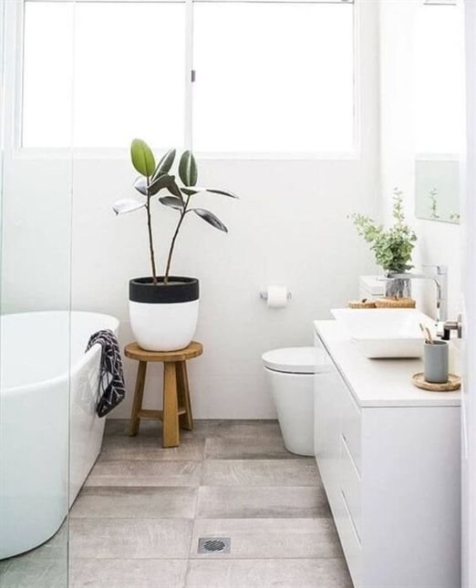 a small Nordic bathroom with a wood tiile floor, a white vanity, an oval tub and potted greenery