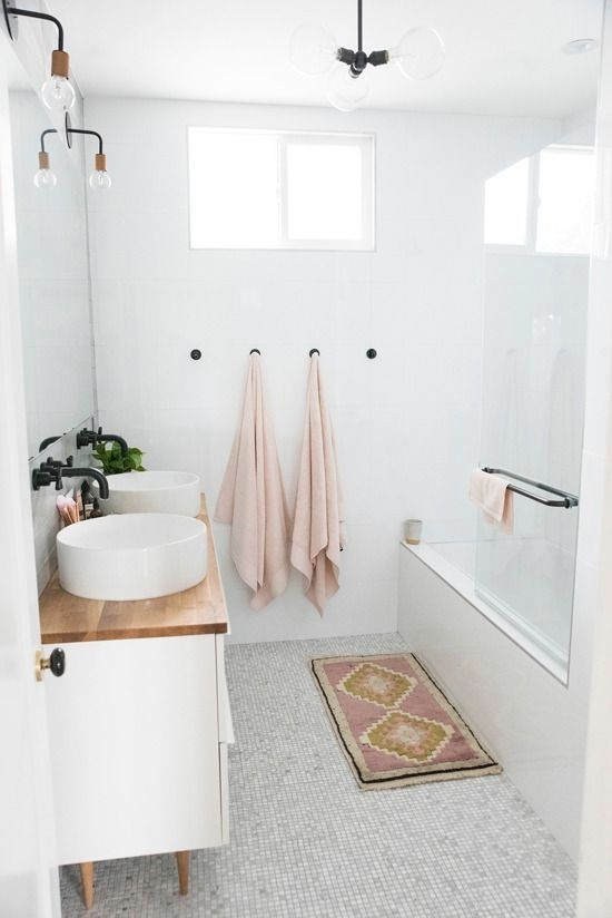 a small Scandinavian bathroom with blush towels, a pink rug, a vanity with a wooden top and sinks