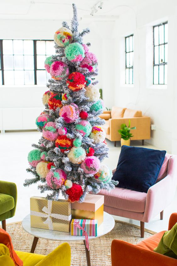 a snowy Christmas tree decorated with colorful pompoms and with colorful gifts is a very nice and bright idea