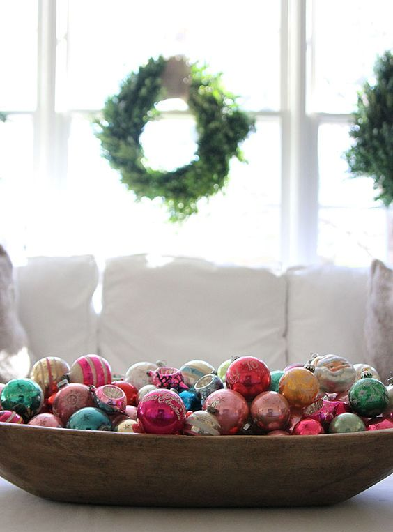 a stylish Christmas decoration of a vintage dough bowl and colorful vintage Christmas ornaments
