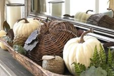 a stylish rustic fall decoration with a dough bowl, real and fake pumpkins of various materials plus greenery