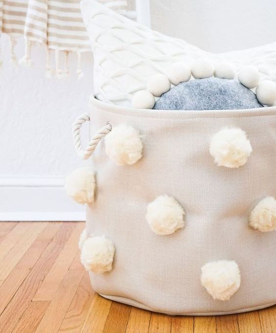 a tan fabric basket with white pompoms and white rope handles is a stylish storage piece to rock