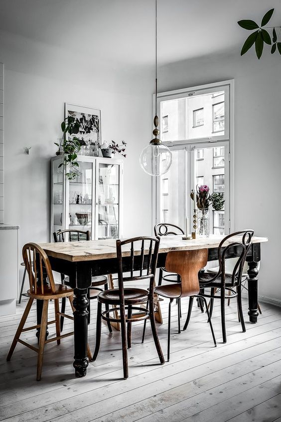 a vintage Nordic dining room with a vintage black dining table, mismatching chairs, a white glass cupboard and lots of potted plants