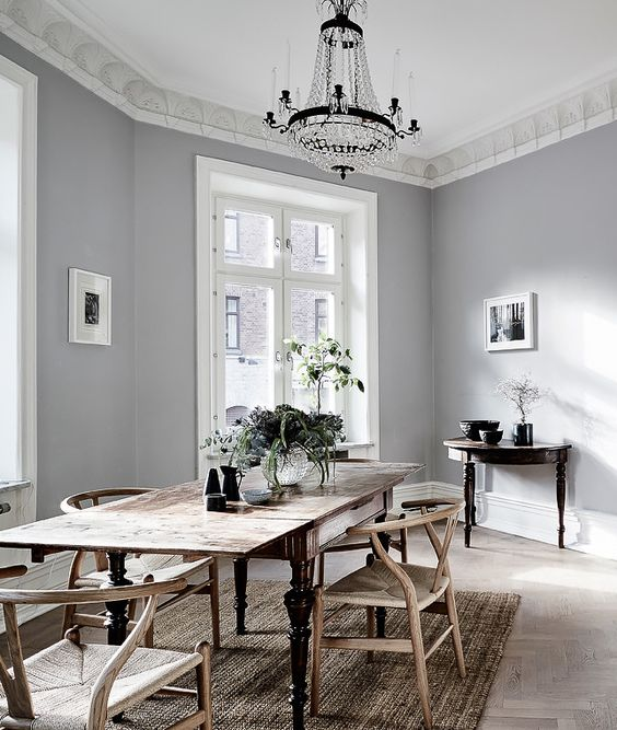 a vintage Scandinavian dining room with a vintage shabby table and woven chairs, a crystal chandelier and a jute rug