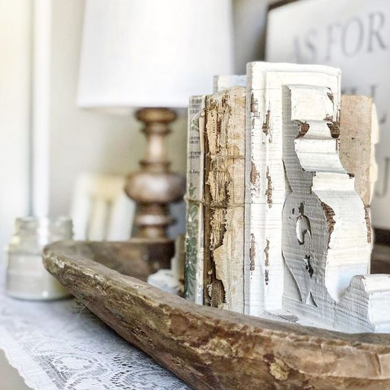 a vintage dough bowl with antique books and bookends brings a touch of vintage and elegance