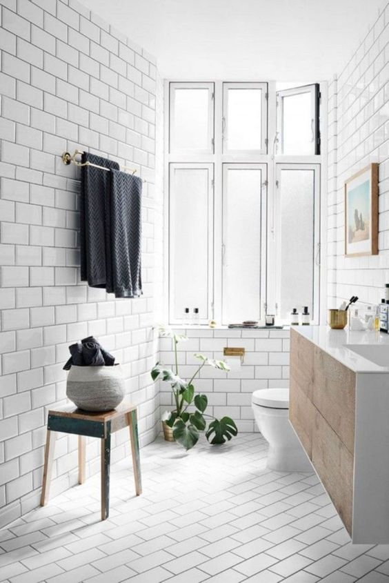 a welcoming Scandi bathroom with vintage touches, a wooden vanity =, towels and a large window for natural light