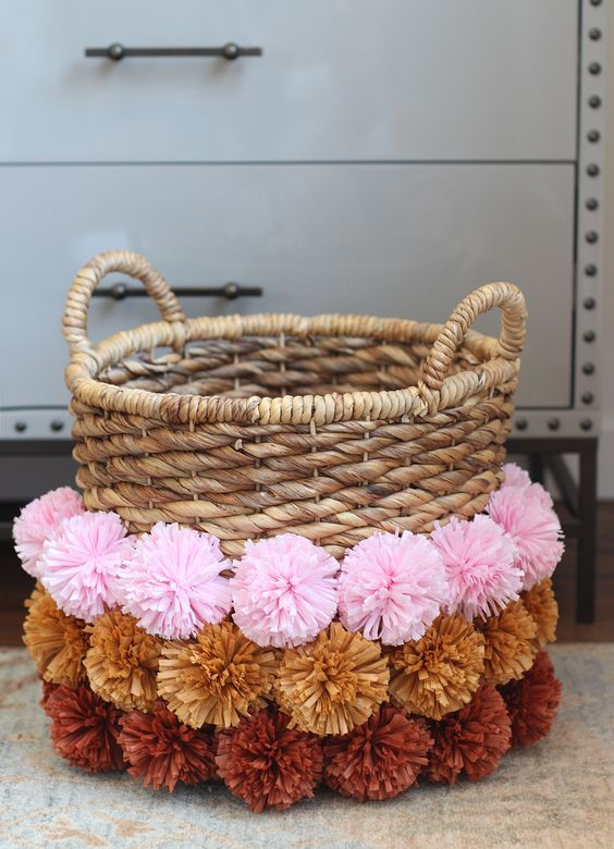 a woven basket decorated with colorful pompoms is a nice storage unit that you may use