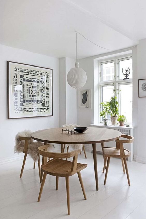 an airy Scandinavian dining nook with a round table and matching wooden chairs, a statement artwork and a pendant lamp