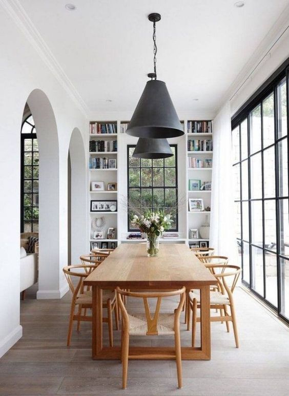 an elegant Scandinavian dining room with a stained table and chairs, built-in shelves and much natural light through the windows